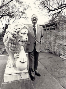 Roy Kumpe stands with the historic Lion statue that guards the Lions World Services for the Blind (LWSB) campus. at the corner of 28th Street