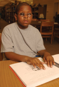 Young boy reading braille.