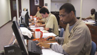 Men sitting at a row of computers, transcribing braille