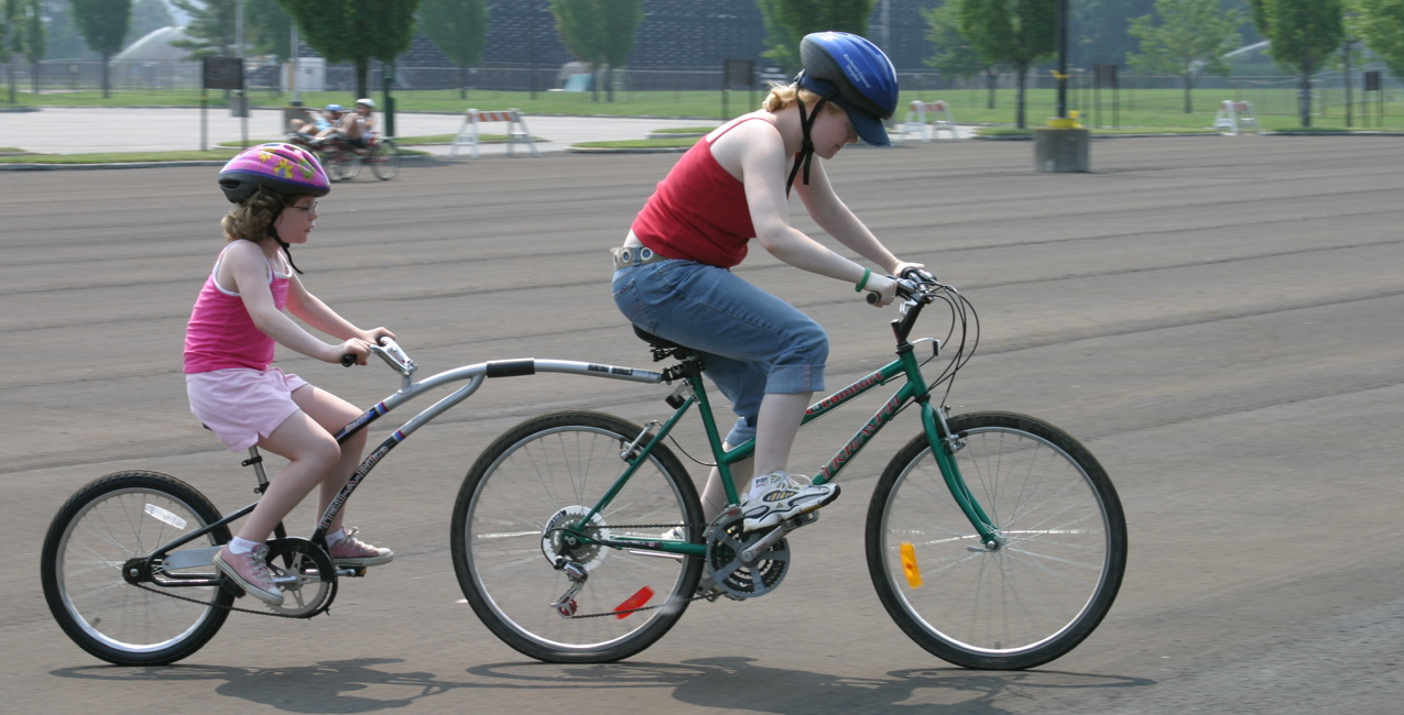 A teen and a child ride a Tag Along bike.