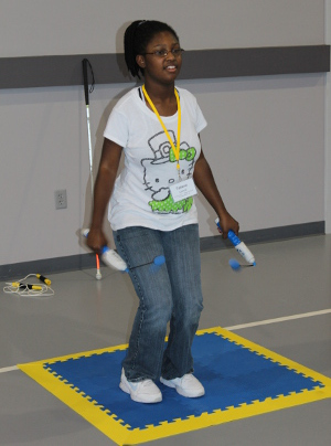 A teen jumps rope using a ropeless jump rope; she is on an anti shock orientation mat.