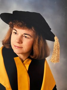 Ann MacCuspie wearing yellow and black academic robes and cap